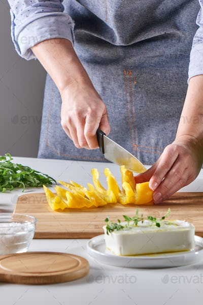 Woman's hands are cutting organic peppers on a wooden board on a gray table. Cooking salad