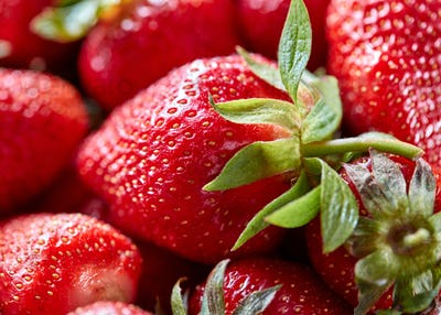 Closeup of ripe strawberries with green leaves. Organic freshly picked healthy berry. Food