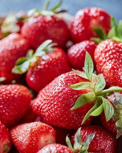 Closeup of juicy red strawberry berries with green stems. Organic healthy food