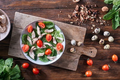 A plate of salad from boiled meat, quail eggs, spinach and tomatoes on a wooden board on the kitchen