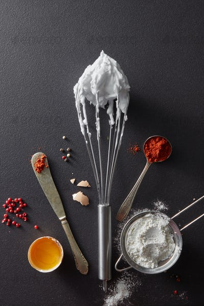 A set of knife with pepper, sieve with flour, metal whisk and boiled eggs on a black concrete