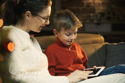 Boy using a tablet with his mother
