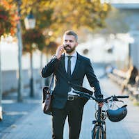 Businessman commuter with bicycle walking home from work in city, using smartphone.