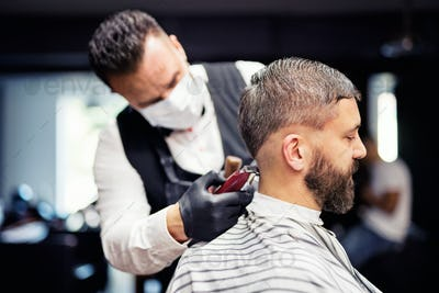Hipster man client visiting haidresser and hairstylist in barber shop.