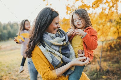 A young family with two small children in autumn nature.