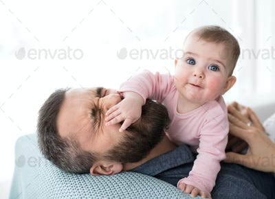 Mature father playing with baby daughter sitting indoors, having fun.