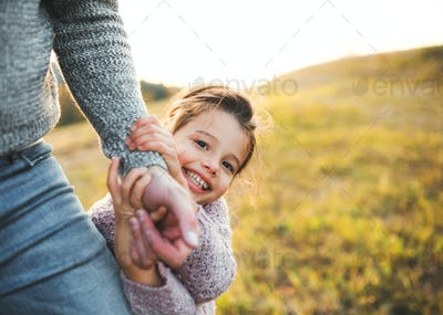 A small girl with unrecognizable father in autumn nature, having fun.