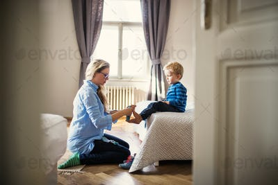 A young mother putting socks on toddler son inside in a bedroom.