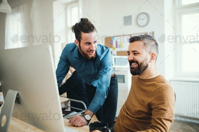Two young male businesspeople with computer talking in a modern office.