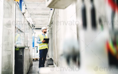 An industrial man engineer with clipboard in a factory, working. Copy space.