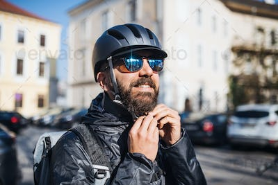 Male courier with sunglasses delivering packages in city.