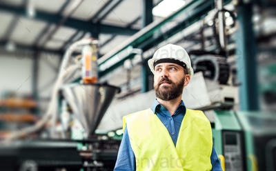 A portrait of an industrial man engineer standing in a factory. Copy space.