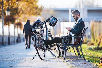 Businessman commuter with bicycle sitting on bench in city, using smartphone.