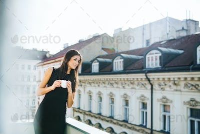 Young businesswoman with cup of coffee standing on a terrace in city. Copy space.