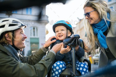 A small toddler boy with helmet and young parents outdoors in city.
