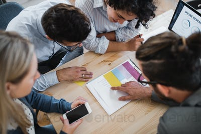 A top view of group of young businesspeople working together in a modern office.