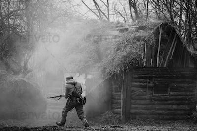German Wehrmacht Infantry Soldier In WW II Running On Battlefiel