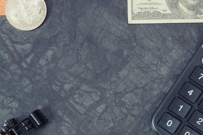 Bitcoins, calculator, dollar and miniature excavator