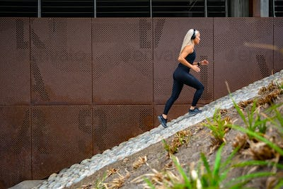 Fit sports women running interval workout in stairs against a metal wall in city