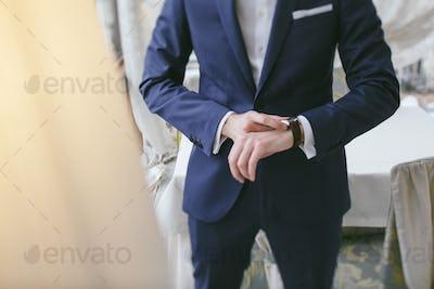 elegant groom in a hotel room