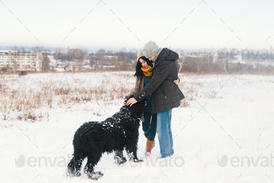 A couple enjoying winter while walking their big black dog havin