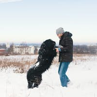 Excited man playing in the snow with his best friend, black dog