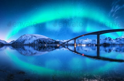 Bridge and aurora borealis over snowy mountains