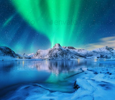 Aurora borealis over snowy mountains, frozen sea coast