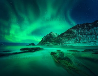 Aurora borealis, snowy mountain and sandy beach with stones