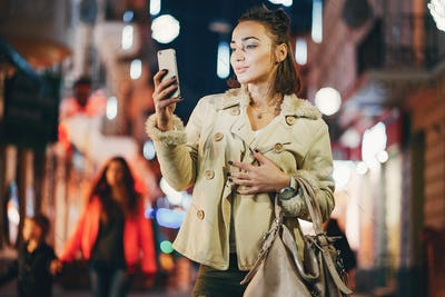 girl checking her phone outside at night