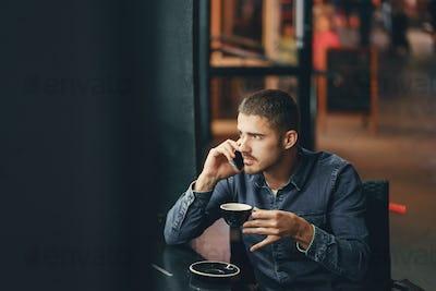 man using phone inside a restaurant