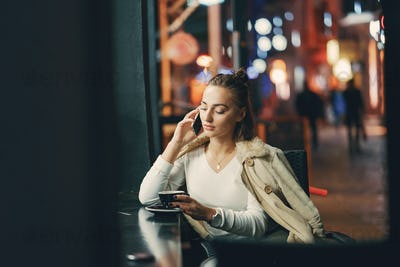 girl sitting outside a cafe using her phone
