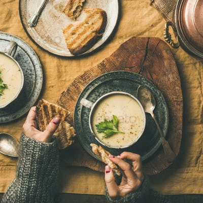 Celery cream soup and female hands with bread, square crop