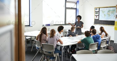 Female High School Tutor Standing By Table With Students Teaching Lesson