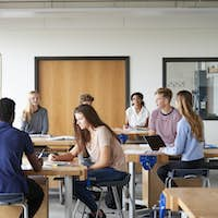 Class Of High School Students Sitting At Work Benches Listening To Teacher