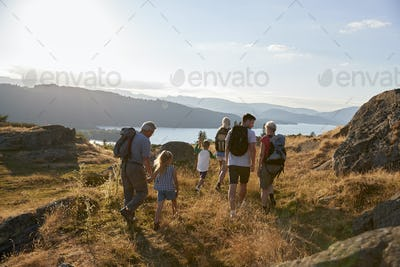 Rear View Of Multi Generation Family Walking On Top Of Hill On Hike