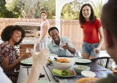 Young adult friends sitting outdoors for lunchtime barbecue