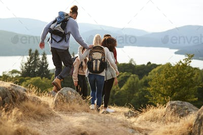 A group of mixed race young adult friends descending after a mountain hike, back view