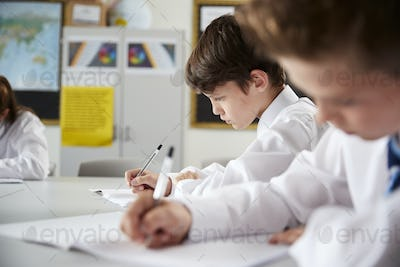 High School Students Wearing Uniform Sitting And Working Around Table In Lesson