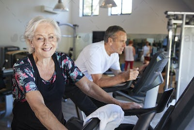 Portrait Of Active Senior Woman Resting After Exercising On Cycling Machines In Gym
