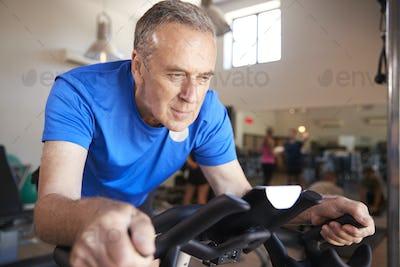 Senior Man Exercising On Cycling Machine In Gym