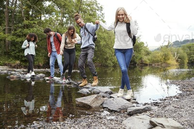 Multi ethnic group of five young adult friends hold hands walking on rocks on a hike