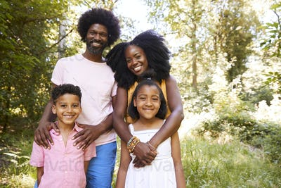 A black couple and their two kids in a forest, portrait