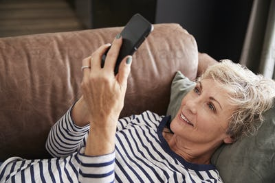 Senior woman lying on couch using phone, elevated close up