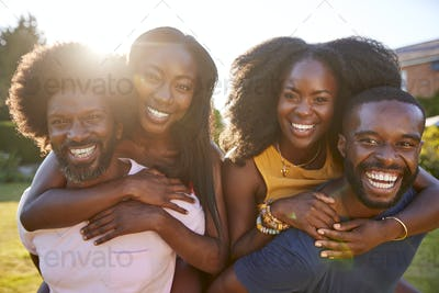 Two black couples, men piggybacking their partners, close up