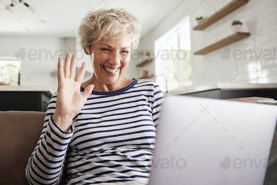 Senior woman video calling on a laptop, waving at screen