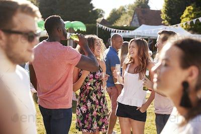 Group Of Friends Enjoying Drinks At Summer Garden Fete