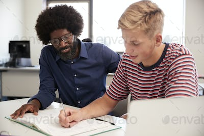 High School Tutor Giving Male Student One To One Tuition At Desk  In Classroom