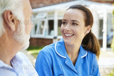 Senior Man Sitting On Bench And Talking With Nurse In Retirement Home