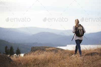A young adult Caucasian woman hiking alone on a mountain peak, back view